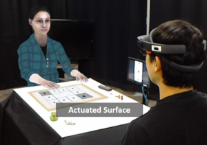 The Physical-virtual Table: Exploring the Effects of a Virtual Human's Physical Influence on Social Interaction